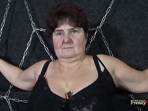 Chained beamy granny Hana gives a blowjob standing on her knees